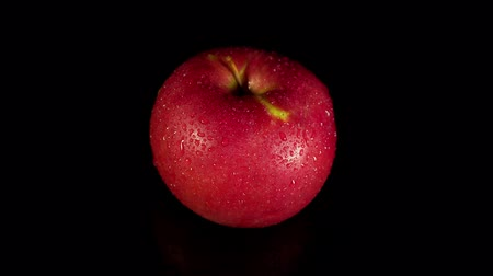 Close-up of a fresh red Apple with droplets rotate counterclockwise on a black background, seamless looping. Stok Video