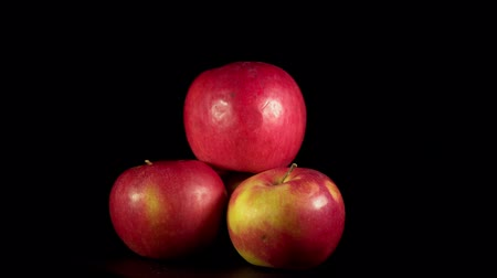 Red apples rotate counterclockwise, fresh organic fruits isolated on black background, seamless looping.
