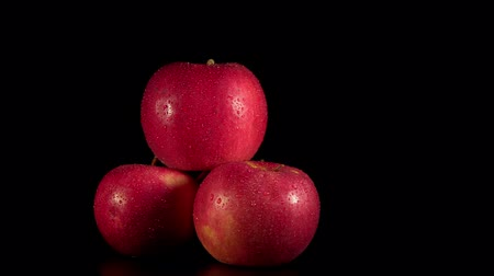 Closeup of ripe red apples with water droplets rotate counterclockwise on black background, seamless looping.
