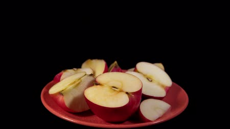 Slices of red appetizing apples on a coral plate rotate on a black background, seamless looping.