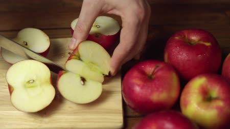 Closeup of a man cuts a red apple into halves and quarters with a knife. Ripe juicy fruit cut into pieces on a chopping wooden board,dolly shot. Stok Video