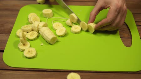 Closeup of a man cuts a yellow banana into pieces with a knife. Ripe juicy fruit cut into slices on a chopping board, dolly shot.