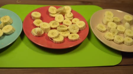 Beige, red and blue plates with appetizing round slices of bananas stand on a wooden table, the camera moves from right to left. Stok Video