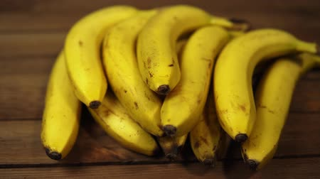 A bunch of yellow ripe mouth-watering bananas lie on a wooden table, the fruits are covered with water drops, dolly shot.