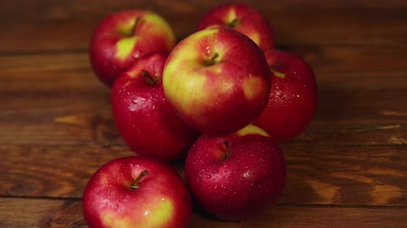 Many red, wet, mouth-watering apples lie on a wooden table, the camera slowly turns around the fruit.