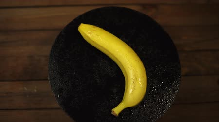 One delicious wet banana rotates clockwise on a black plate on a wooden table, seamless looping.