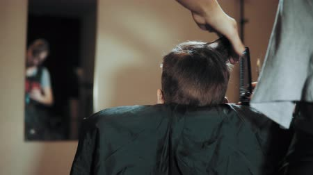 boy having her hair cut at the hairdressers. Hairdresser trimming male dark hair with scissors in beauty salon.