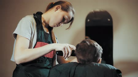 Hairdresser makes hair hair machine for a boy who sits in front of a mirror and watches the process. Haircut for children hair trimmer and comb at the hairdresser, view from the back. Stok Video