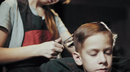 Close-up of a hairdresser doing a hair-dressing machine for a boy. Haircut of a childrens hair trimmer and comb at the hairdresser.