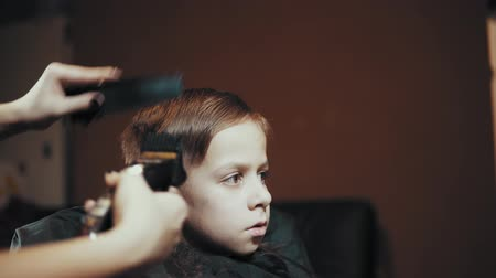 Close-up of a hairdresser doing a hair-dressing machine for a boy. Haircut of a childrens hair trimmer and comb at the hairdresser, side view. Stok Video