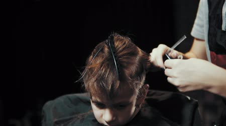 Close-up of a female barber doing a haircut with scissors and a hairbrush for a boy. Haircut childrens hair at the hairdresser.