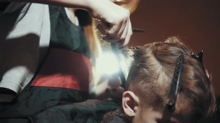 makas : Close-up of a female barber doing a haircut with scissors and a hairbrush for a boy. Haircut childrens hair at the hairdresser.