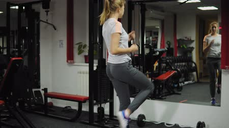 kardiyoloji : View from the back on a young healthy woman performing cardio training using a step-board in front of the mirror. Sport and health concept. Stok Video