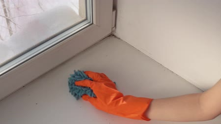 sıkıcı iş : A hand in an orange protective glove with a blue damp rag washes and cleans the window sill from dust and dirt. The human wipes the sill to reduce allergens and give freshness to the room. Stok Video