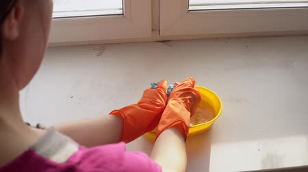 sprzątanie : Hands in orange gloves squeeze and wringing a blue microfiber rag into a yellow bowl filled with water which stands on the windowsill, a look over the shoulder of a woman. Wideo