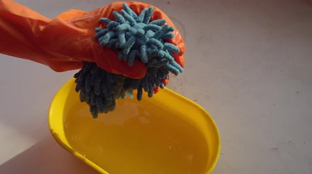 szorítás : Female hands in orange gloves squeeze and wringing a blue microfiber rag into a yellow bowl filled with water.
