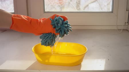 szorítás : Hands in orange gloves squeeze and wringing a blue microfiber rag into a yellow bowl filled with water which stands on the windowsill.