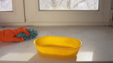 mopping : A hand in an orange protective glove with a blue damp rag washes and cleans the window sill from dust and dirt. The human wipes the sill to reduce allergens and give freshness to the room. Stock Footage