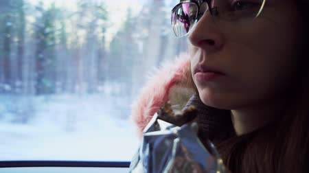 way out : Pensive brunette young woman with glasses eat energy bar and looks out the window during a winter journey by train. Stock Footage