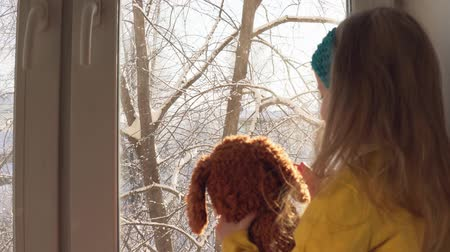 plüss : A cute little blonde girl with a blue bandage looks out the window at the winter landscape, sitting on the windowsill. Happy baby playing with a plush brown toy, dolly shot.