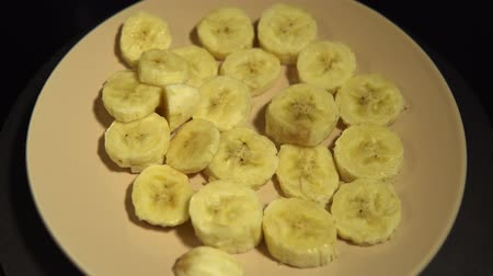 banan : Closeup of banana slices on a beige plate rotate on a black background, seamless looping.