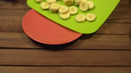 разделочная доска : Someone pours round banana slices from a green cutting board into a red ceramic plate.