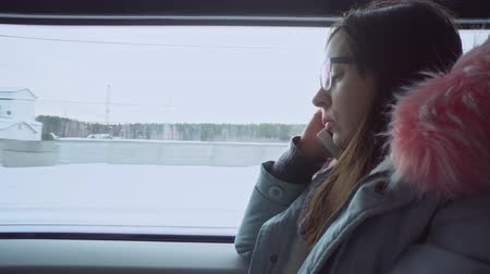 call out : A young woman with glasses and a warm gray parka talking on the smartphone and looks out the window of a moving train at the winter landscape.