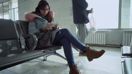 airport bus : A young woman with glasses sits at train station in the waiting room with a smartphone and a small backpack, she is dressed in a gray parka.