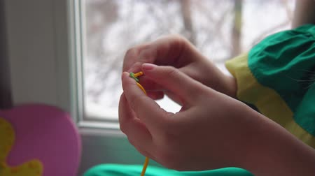 türelem : Closeup of a child inserts a yellow thread into a plastic needle. Cute little girl making a pink handbag. The kid learns to sew. Stock mozgókép