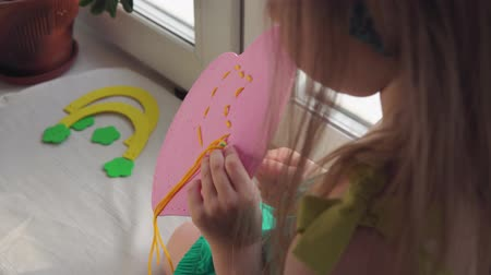 handmade : Cute little girl sews a pink handbag. The child learns to use a needle and thread sitting on the windowsill.