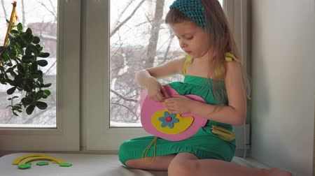 türelem : Cute little girl sews a handbag. The child learns to use a needle and thread sitting on the windowsill on the background of snowy trees, dolly shot.