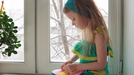 kézzel készített : Cute little girl sews a handbag. The child learns to use a needle and thread sitting on the windowsill on the background of snowy trees. Stock mozgókép