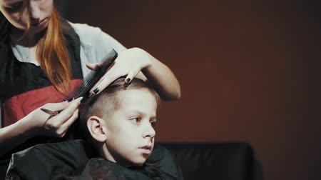 grzebień : Close-up of a female barber doing a haircut with scissors and a hairbrush for a boy. Haircut childrens hair at the hairdresser, side view.