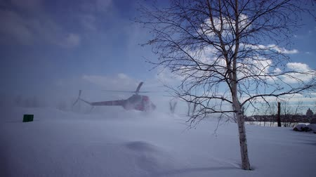 paramedics : Landing civil helicopter MI-2 on the snow-covered helipad clear day in the park. The sound of the engine and propellers.