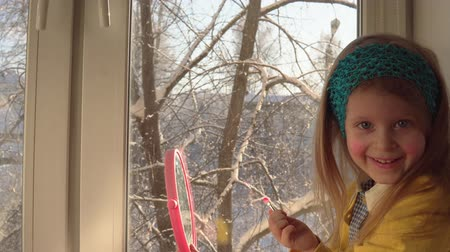corar : Little cute girl in a mustard cardigan and a blue bandage puts makeup looking in a pink mirror, she sits on the windowsill, outside the window is a winter landscape. A child learns to use cosmetics. Stock Footage