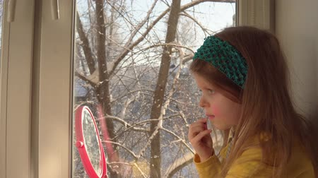 hardal : Little cute girl in a mustard cardigan and a blue bandage puts makeup looking in a pink mirror, she sits on the windowsill, outside the window is a winter landscape. A child learns to use cosmetics. Stok Video