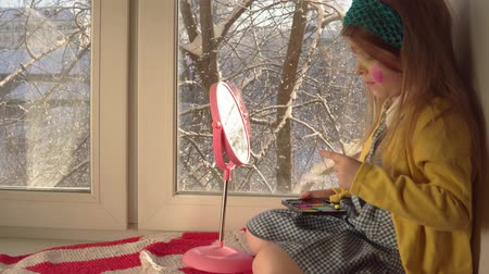 mustár : Little cute girl in a mustard jacket and a blue bandage puts makeup looking in a pink mirror, she sits on the windowsill, outside the window is a winter landscape. A child prepare for a carnival. Stock mozgókép