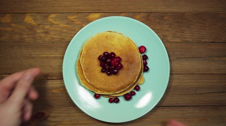 оладья : Someone serves a wooden table, hands correcting a azure plate with appetizing pancakes and red cranberries berries, view from above, the camera moves from left to right.