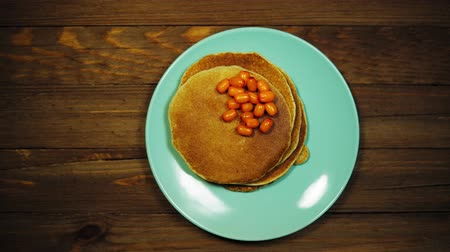 оладья : Top view on a blue plate with appetizing pancakes and orange sea-buckthorn berries on a wooden table, the camera moves from left to right.