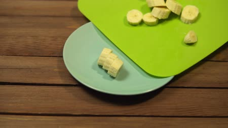 banan : Someone pours round banana slices from a green cutting board into a blue ceramic plate.