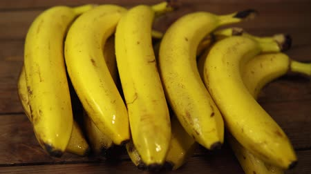 apetitoso : A bunch of yellow ripe mouth-watering bananas lie on a wooden table, the fruits are covered with water drops, dolly shot.
