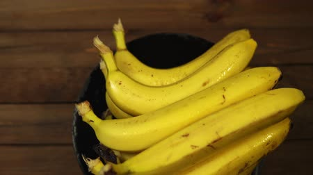 banan : Ripe delicious wet bananas rotate clockwise on a black plate on a wooden table.