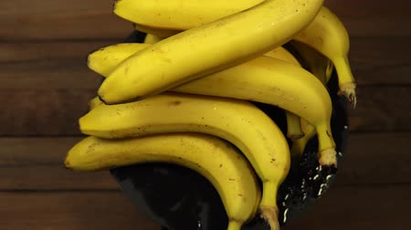 banan : Ripe tasty wet bananas rotate counterclockwise on a black plate on a wooden table.