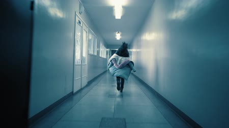 проливая : A young excited woman in a panic runs away from her pursuer along a dark corridor. The girl sheds her jacket to distract the intruder and escapes down the side aisle (russian text: exit) Стоковые видеозаписи
