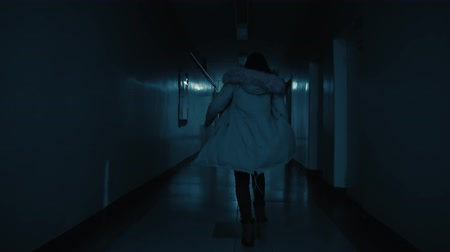 ondergronds : A young excited woman in a panic runs away from her pursuer along a dark corridor. The girl makes a call and escapes away in the side passage. The clock on the wall shows a quarter to eleven pm.
