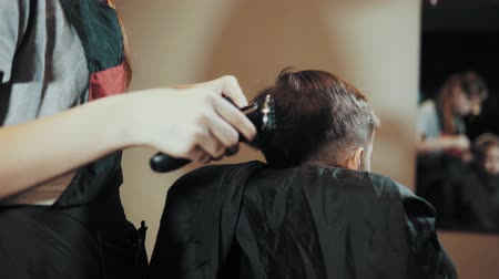 barber scissors : Hairdresser makes hair hair machine for a boy who sits in front of a mirror and watches the process. Haircut for children hair trimmer and comb at the hairdresser, view from the back. Stock Footage