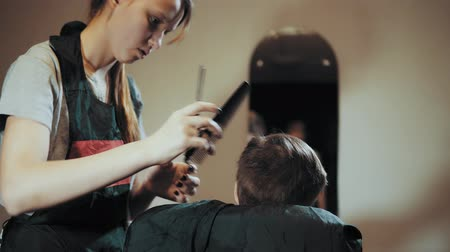 omini : Hairdresser makes hair hair machine for a boy who sits in front of a mirror and watches the process. Haircut for children hair trimmer and comb at the hairdresser, view from the back. Filmati Stock