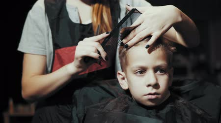 omini : Close-up of a hairdresser doing a hair-dressing machine for a boy. Haircut of a childrens hair trimmer and comb at the hairdresser.