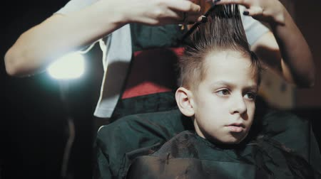 omini : Close-up of a female barber doing a haircut with scissors and a hairbrush for a boy. Haircut childrens hair at the hairdresser.