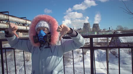 spaliny : Portrait of a young woman in a protective mask and gray park against the background of the pipes of the metallurgical plant on a winter day. Young woman showing thumbs down.